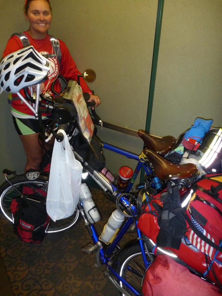 Two bikes and bikers in the motel elevator.