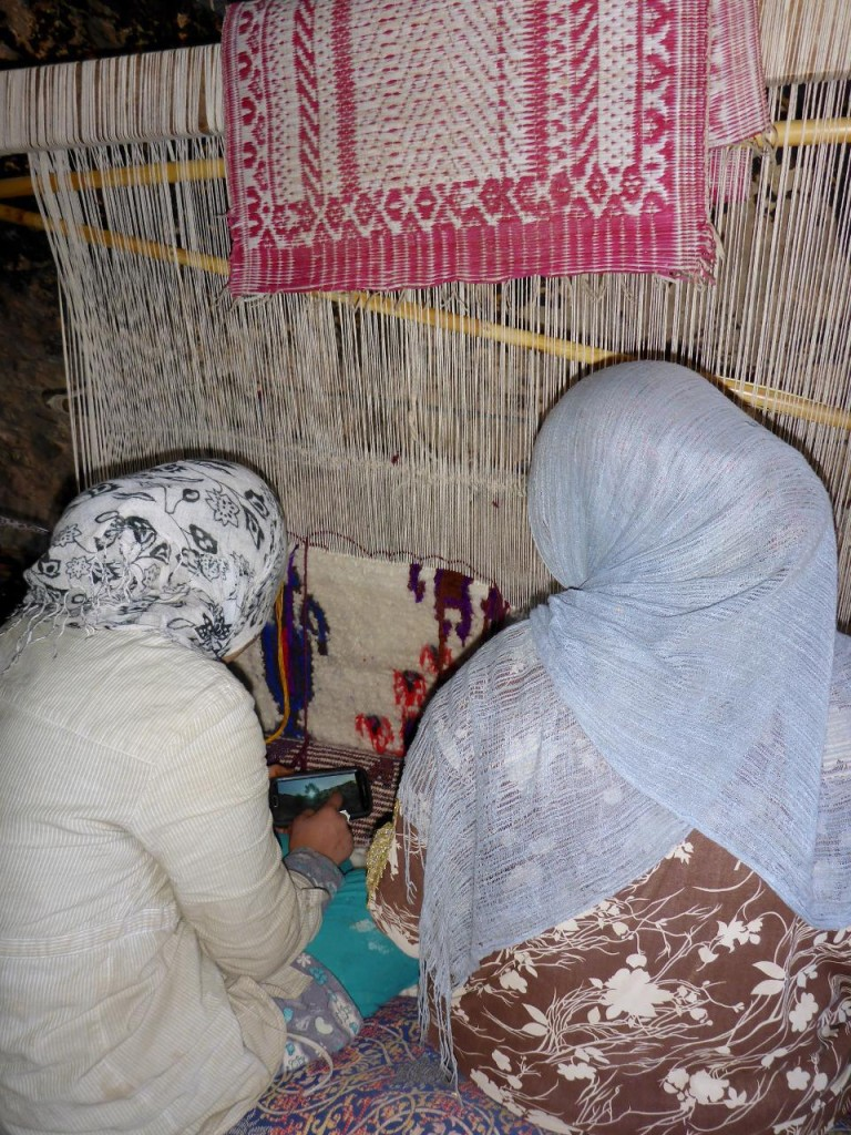 Two nomad girls weaving a carpet.