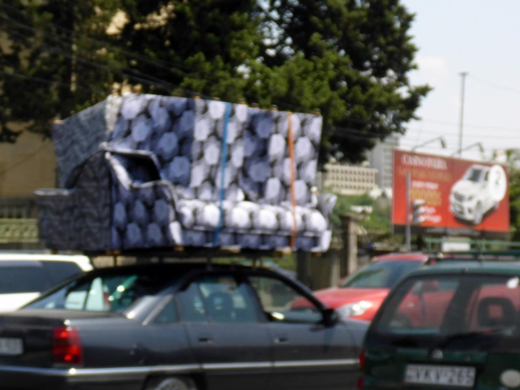 A little blurry but a small car is carrying two couches.