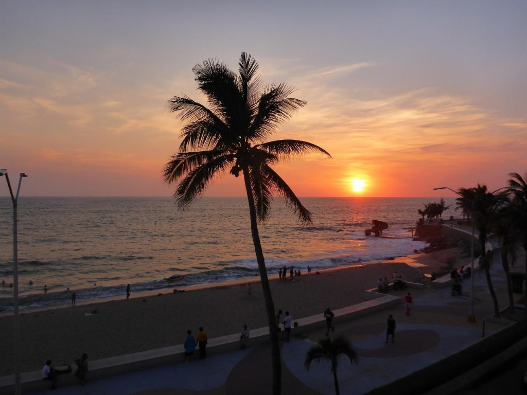 A Mazatlan sunset. Below the sun is a large slide that empties to a pool that is now underwater.