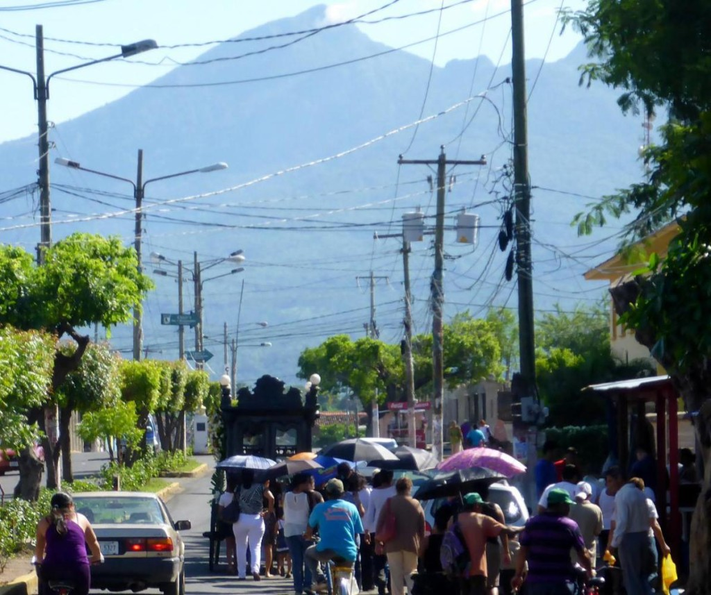 A funeral procession with a volcano in the background.