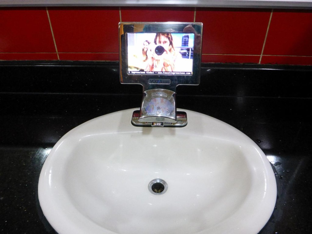 An interesting bathroom sink faucet complete with a tv. Wash hands longer perhaps.