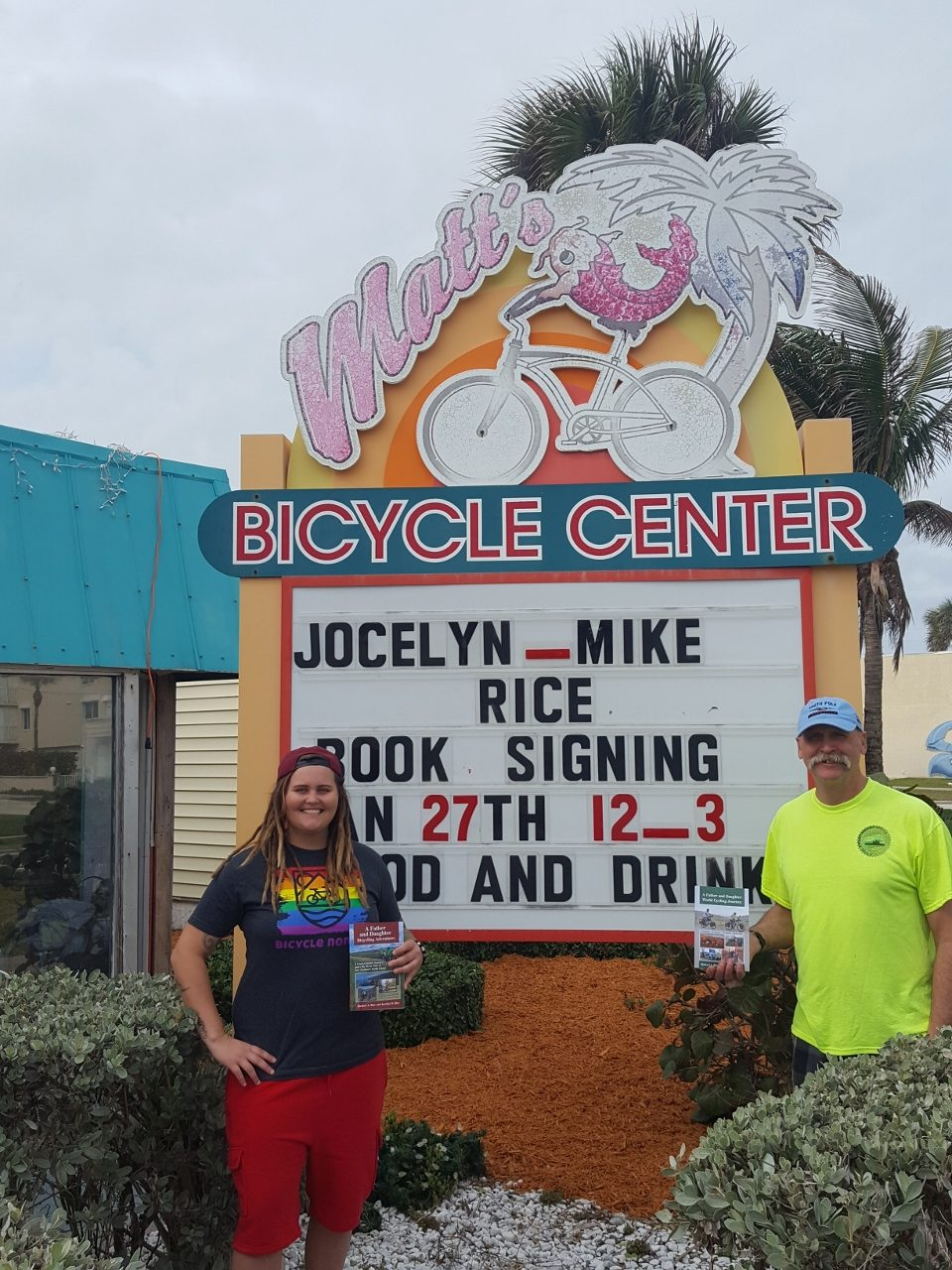 Outside of Matt's Bicycle Center in Cocoa Beach with both of our world journey books.